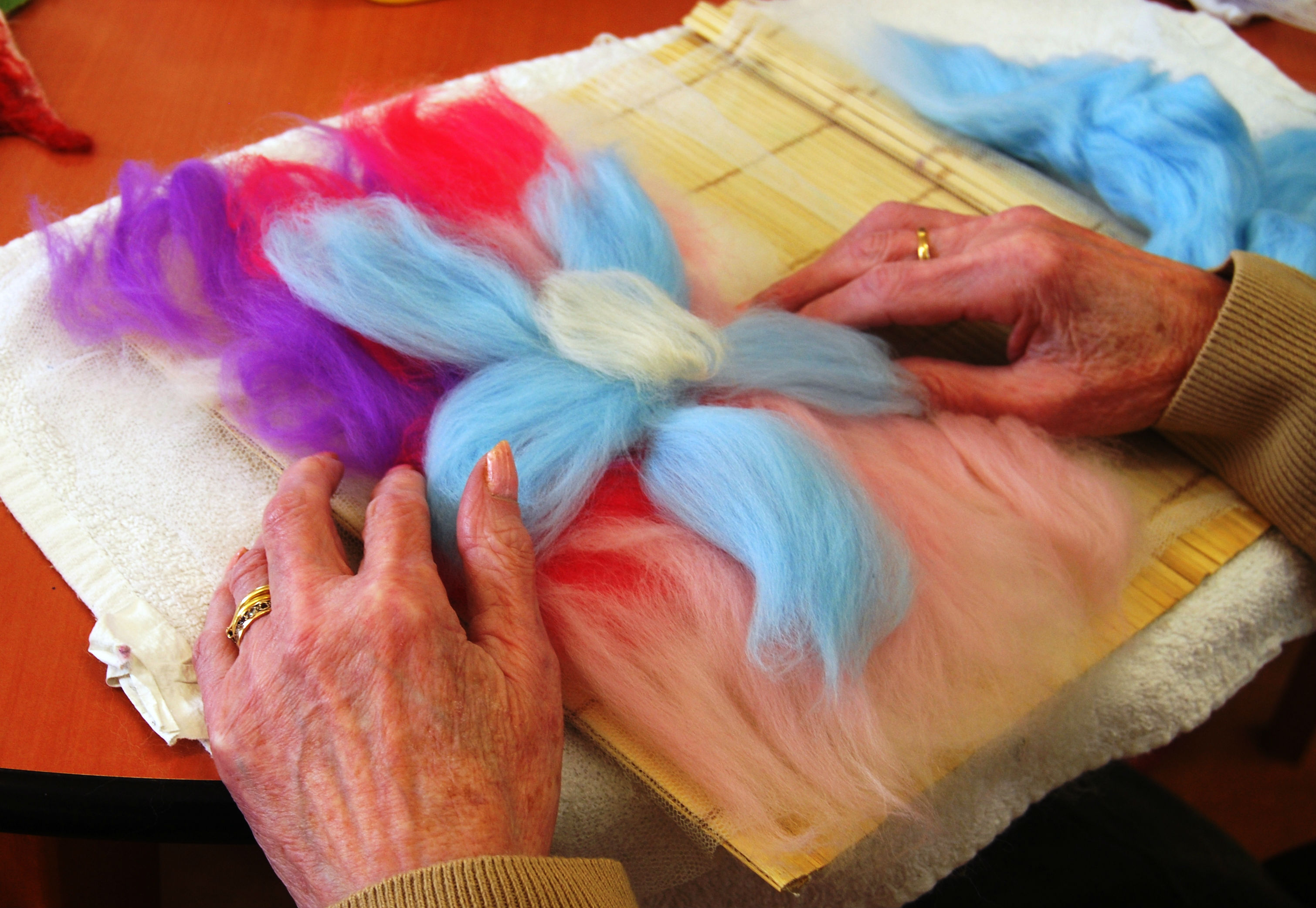 older persons hands work on a felt art project