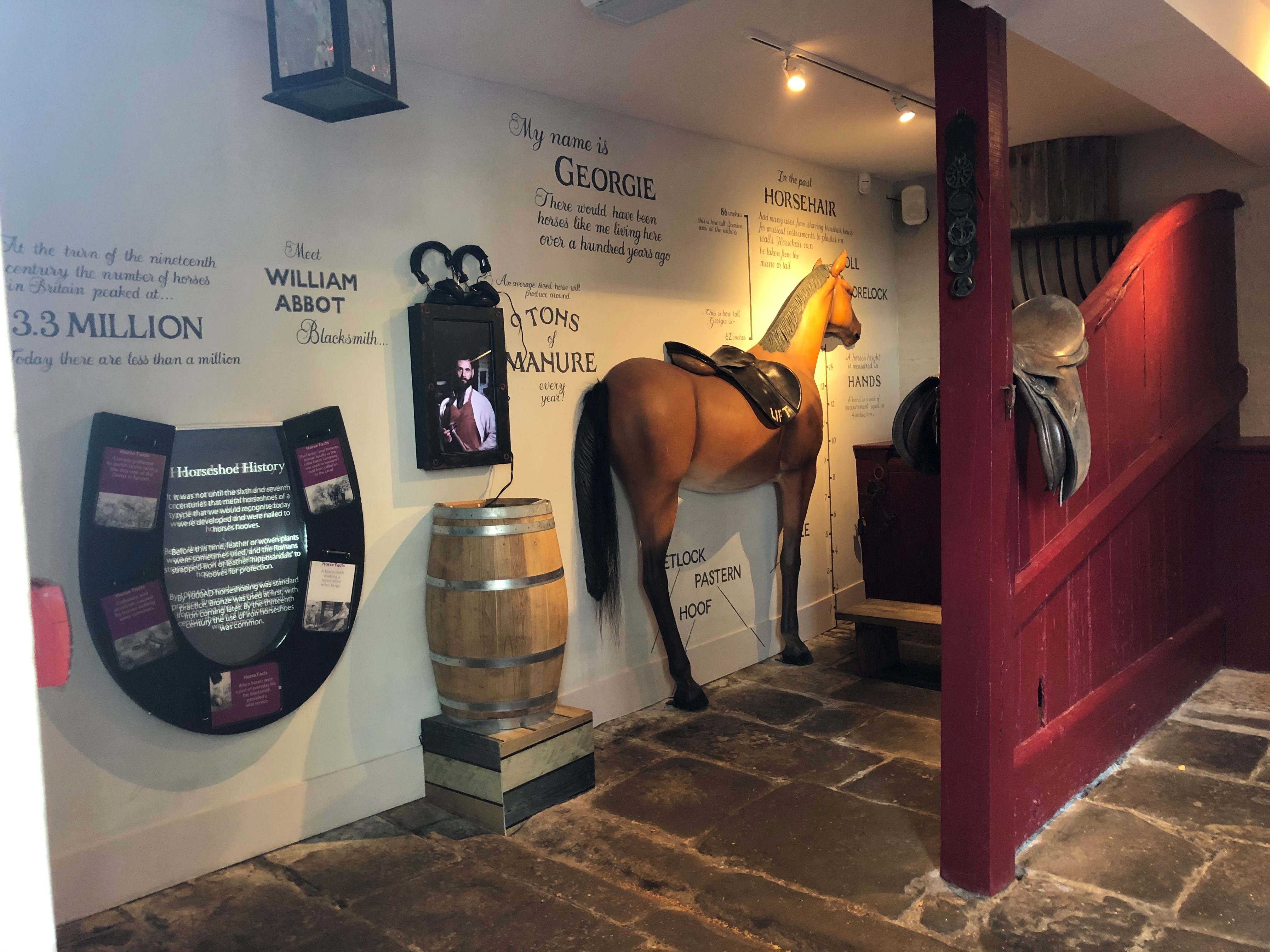 Stable interior with sculptural horse and interactives on wall